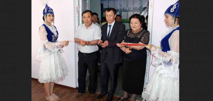 Keneshbek Usenov, Rector of Jalal-Abad State University (left), Ruslan Moldokasymov, EWMI CGP Deputy Chief of Party (second from left), and Irys Beibutova, Coordinator of NPM Resource Center in Bishkek and representative of the Association of NPM Educators (to the right) cut a ribbon to inaugurate the new NPM Resource Center at Jalal-Abad State University.